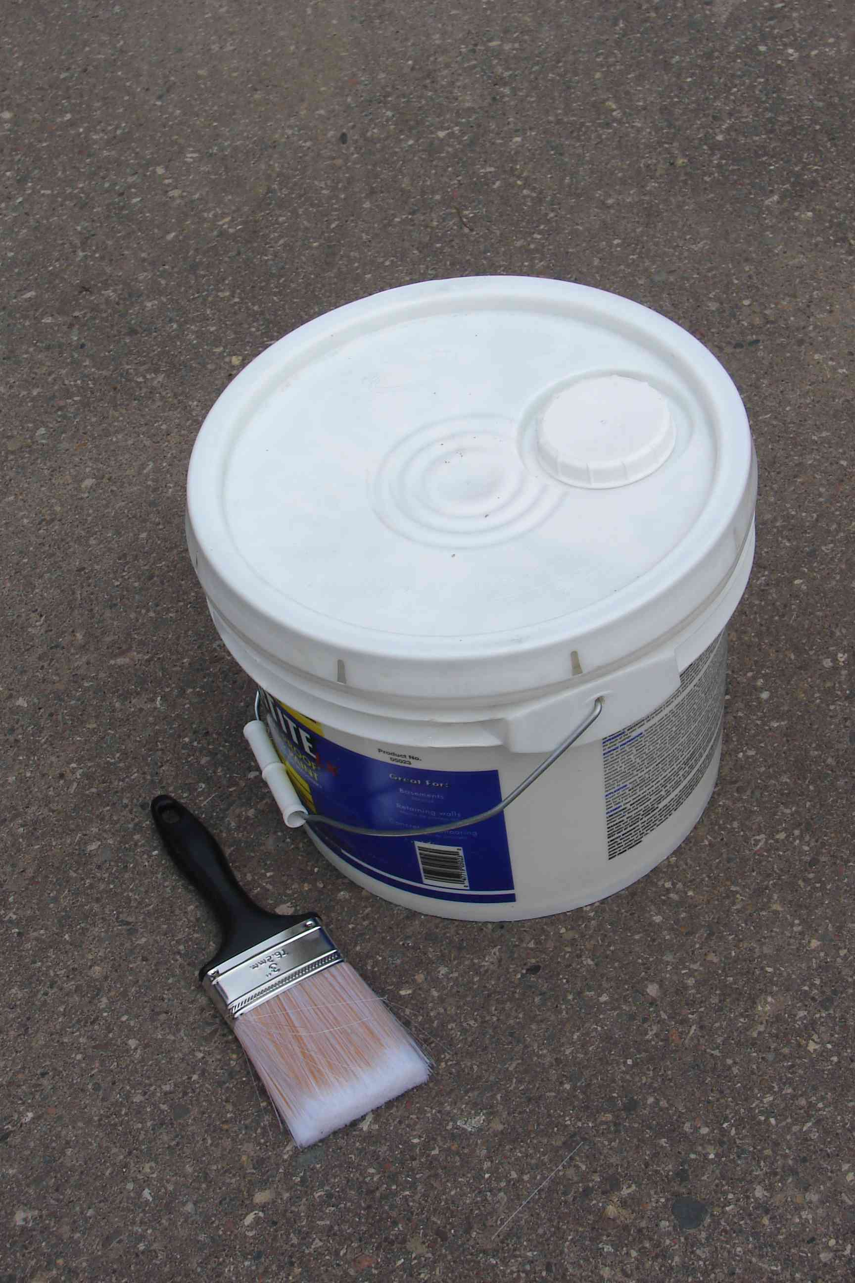 Plastic pail of paint and a paintbrush