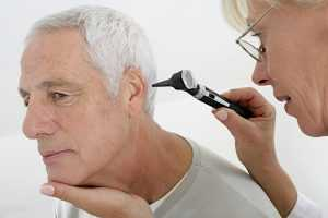 An audiologist checking a patient's ear