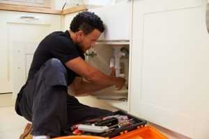 Plumber unclogging and repairing pipes