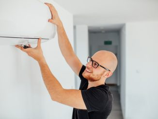 man adjusting AC to change room temp