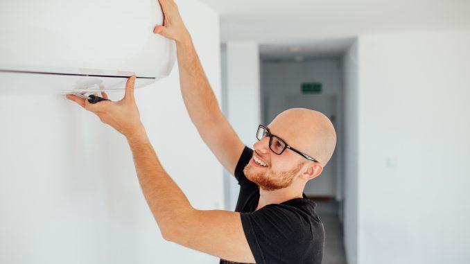 man adjusting AC to change room temp