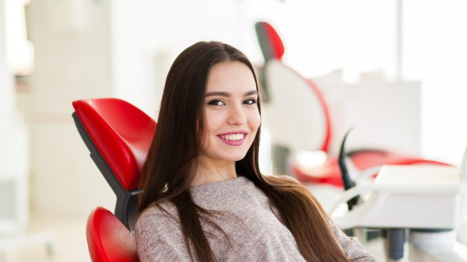 a woman with a bright smile sitting on a dental chair