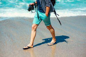 Man in shorts walking on beach