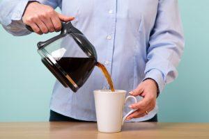 Woman pouring coffee on a mug