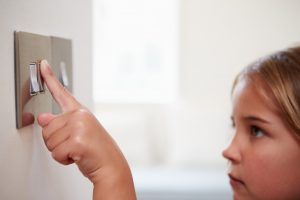 young girl using a light switch