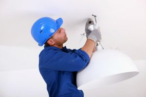 Electrician installing a ceiling light