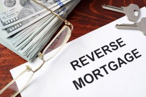 reverse mortgage papers with pair of glasses, dollar bills, and house keys
