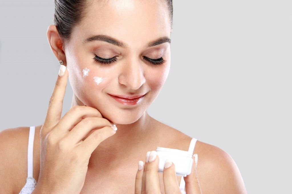 woman applying herbal moisturizer