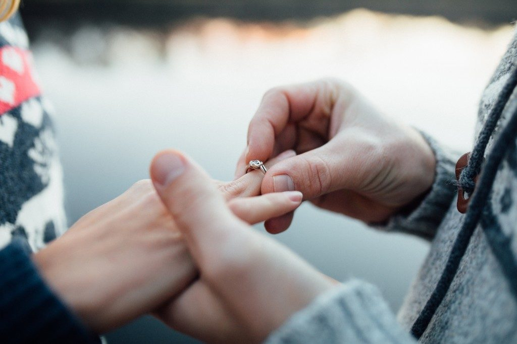 Man putting ring on woman hand