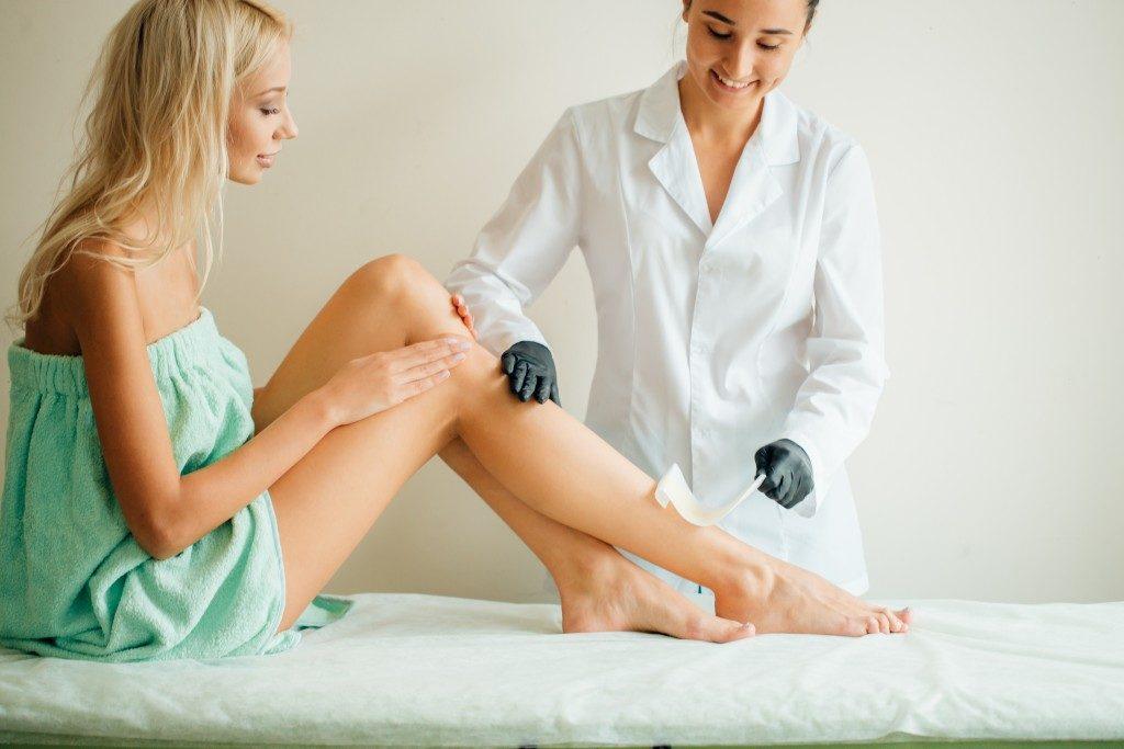 woman getting her legs waxed