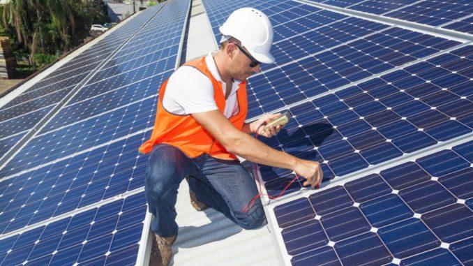 technician checking solar panels