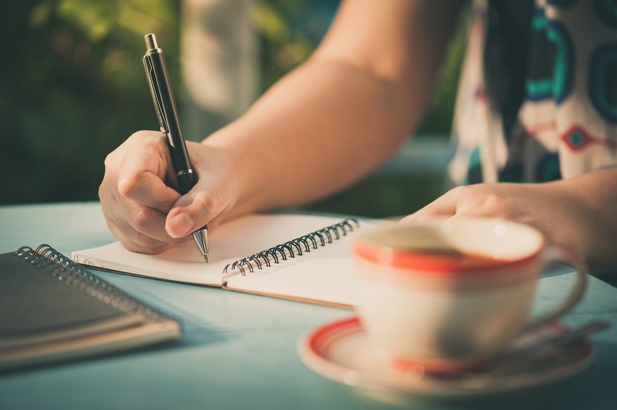 Woman writing on her journal