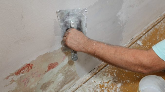 man fixing house wall