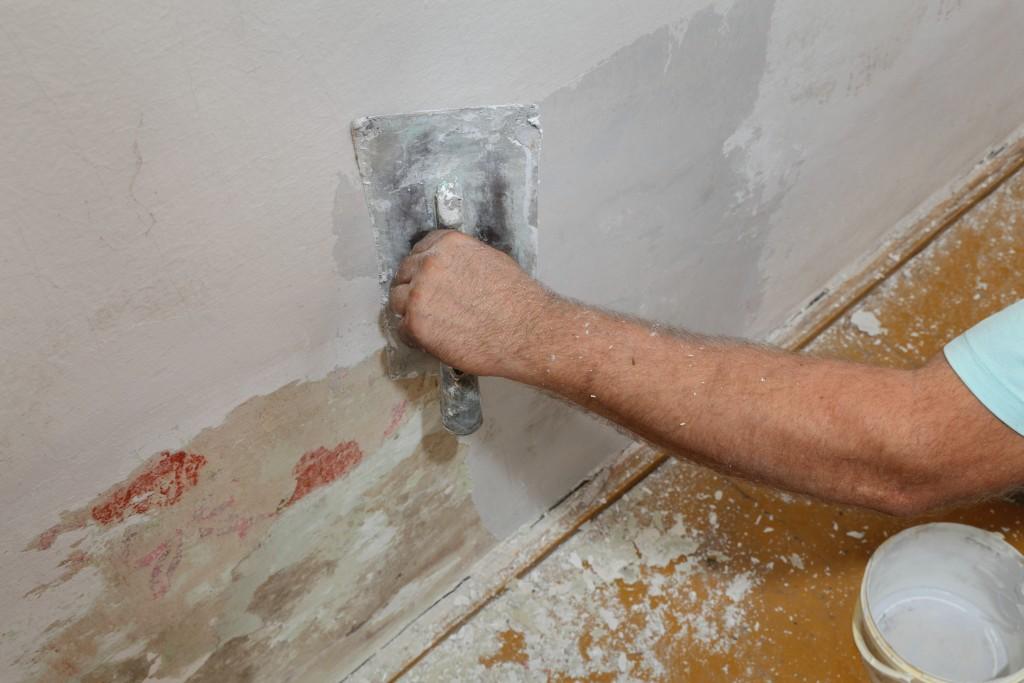 man fixing house wall