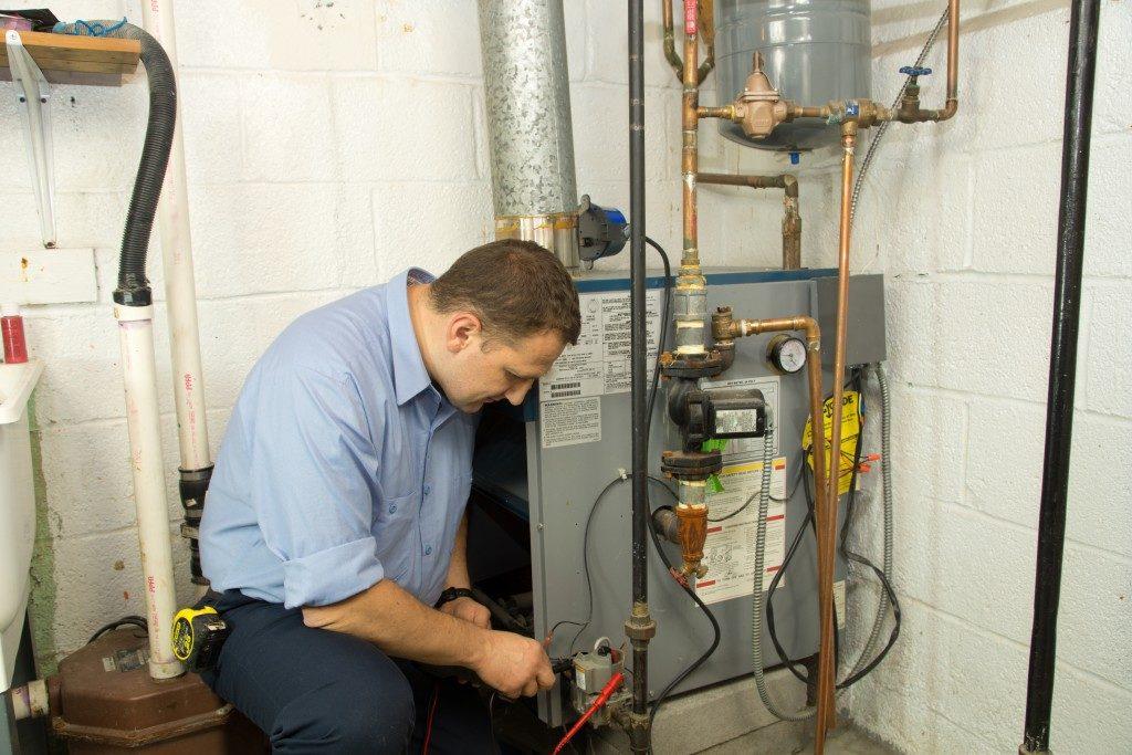 Plumber fixing gas furnace