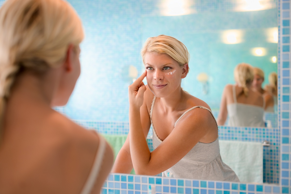 woman putting moisturizer