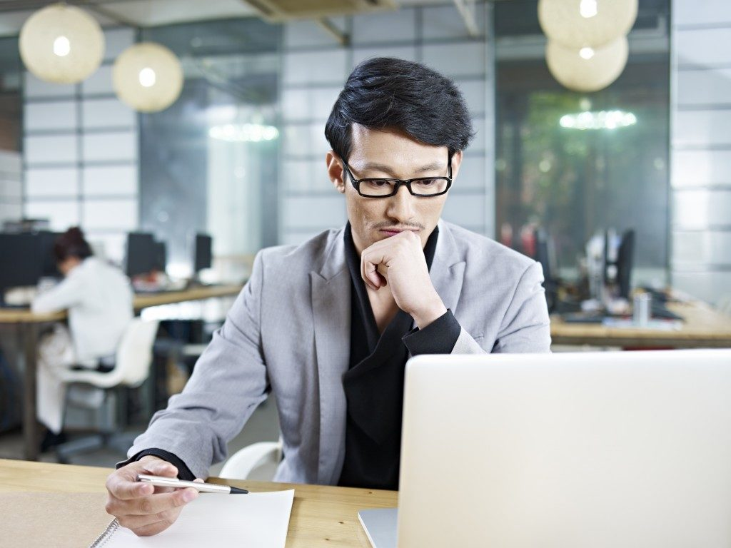 Man looking at his laptop while holding a pen