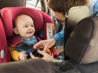 father strapping a child to child seat