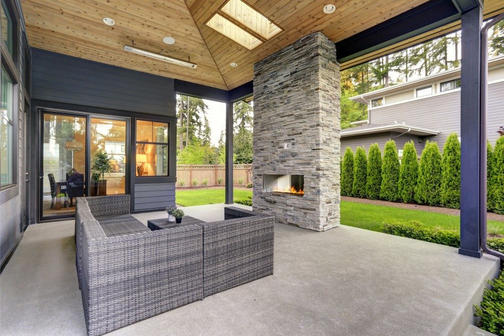 cozy patio with fireplace and rattan sofa