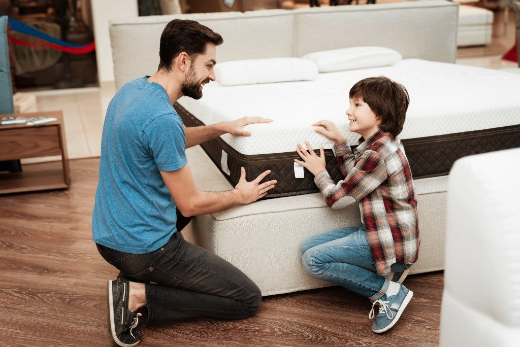 father and son checking mattress