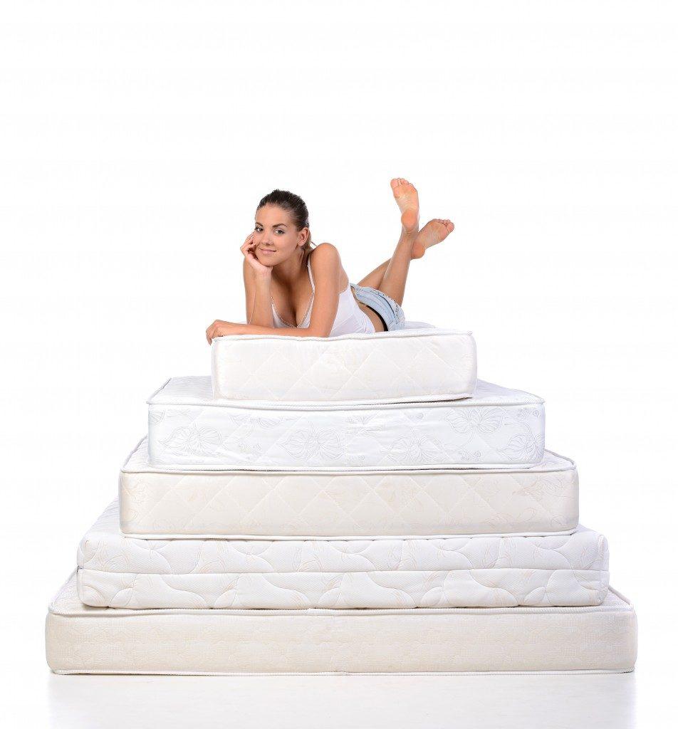 woman lying on many mattresses