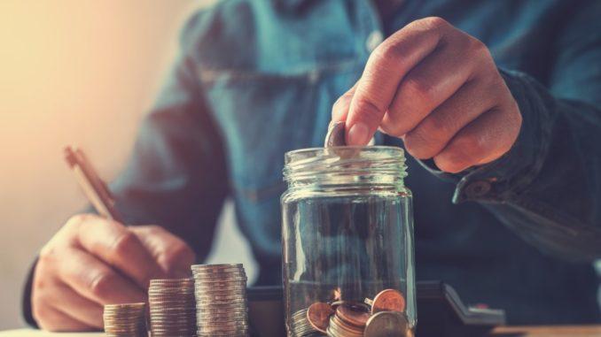 Man saving money putting coins in jar