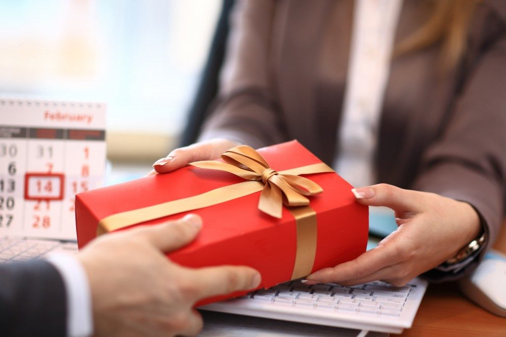 Business man offering a gift to a woman