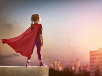 Kid superhero standing at the edge of the building