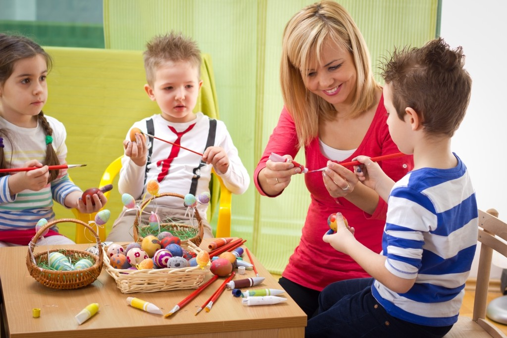 Woman painting eggs with kids
