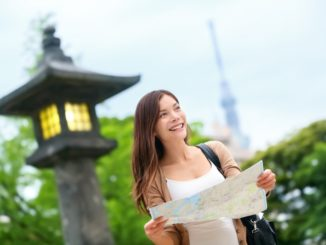 sian tourist woman with map searching for directions with the Tokyo Skytree tower in the background