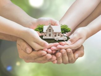 Safe family home model and garden on son daughter children kid guardian mother father hands