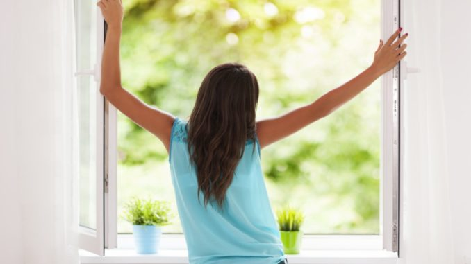 woman opening the window to let fresh air in