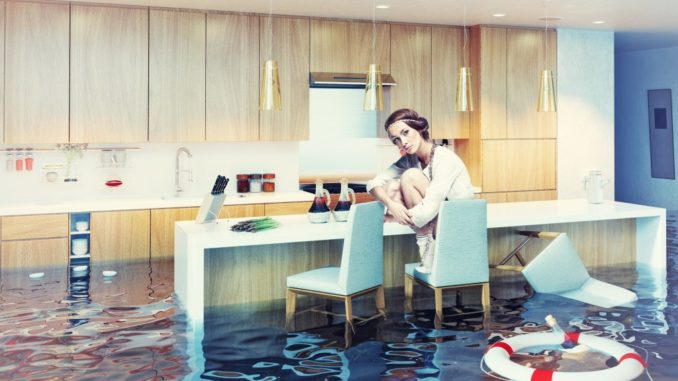 woman sitting on a chair in flooded kitchen interior