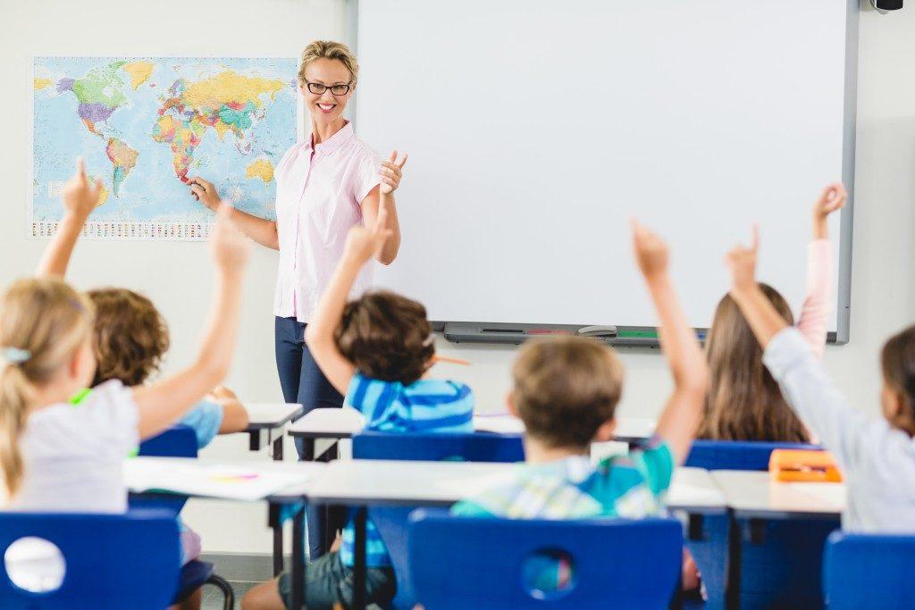Children raising their hands in class