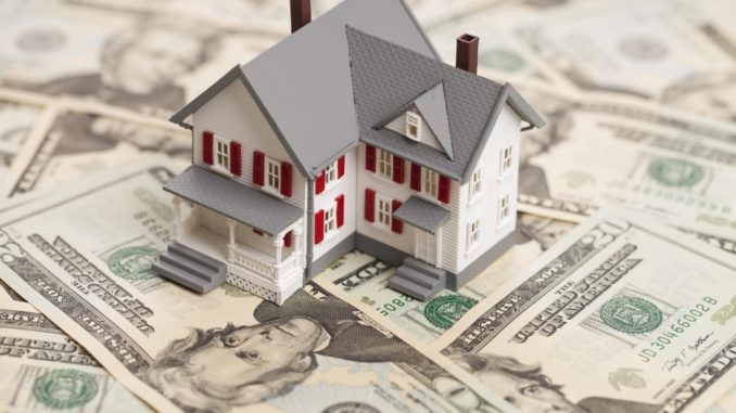 miniature house on top of scattered bills