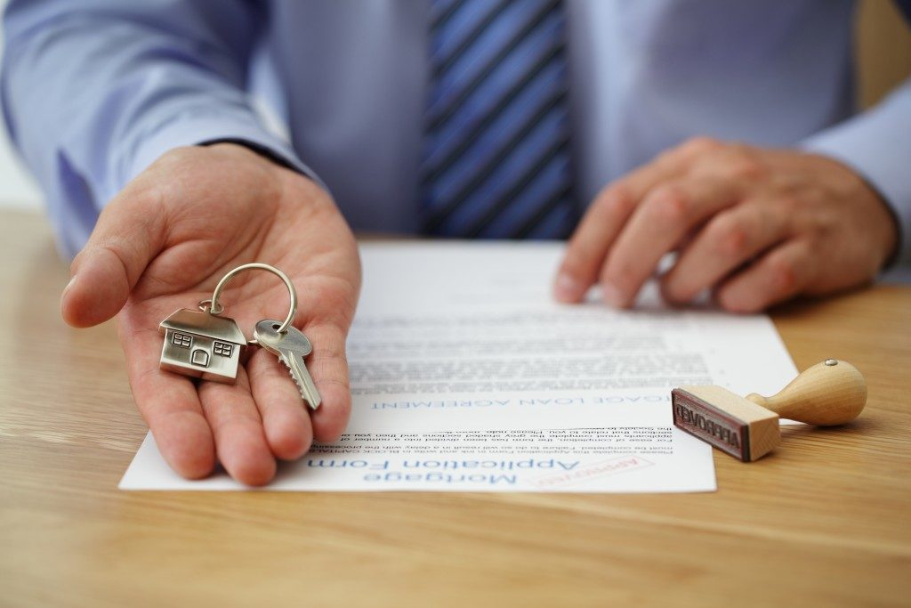 man holding out keys to a house
