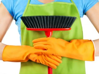 Woman wearing apron and gloves while holding a broom