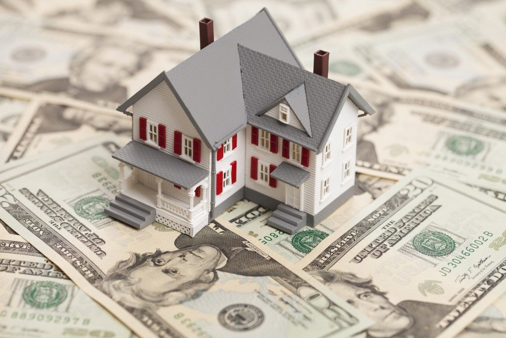 home model and pile of bills
