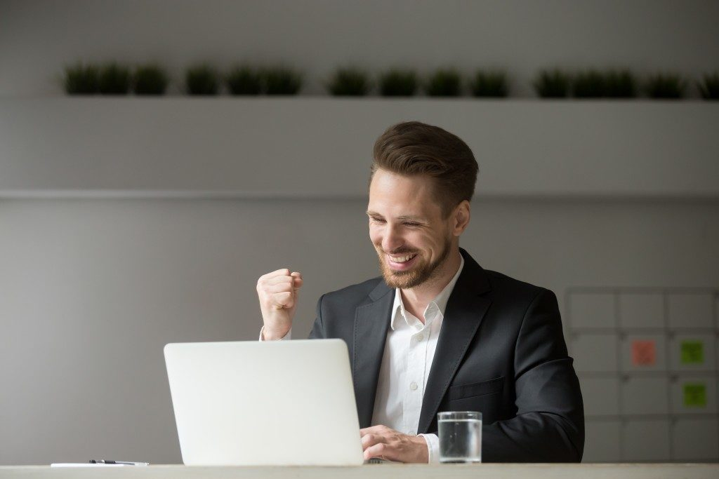 Businessman in excited mood while looking at his laptop
