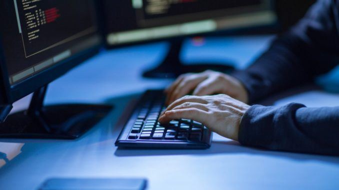 person's hands typing in keyboard