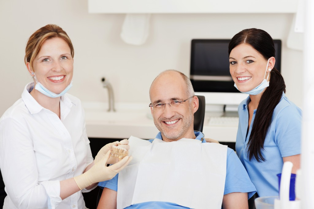 Patient with dentist and dental assistant