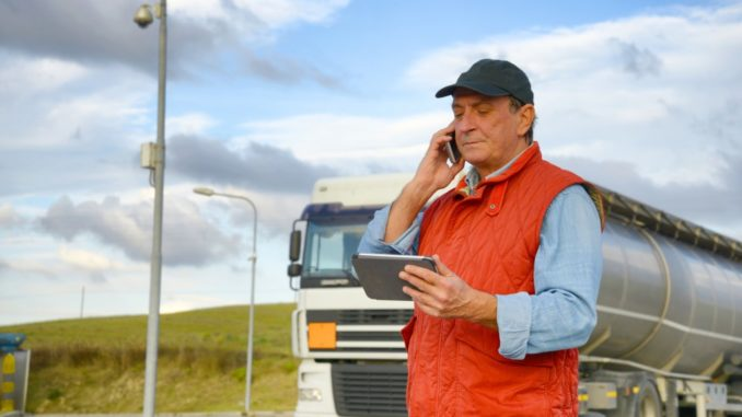 Truck driver talking on the phone while holding a tablet with his truck behind him